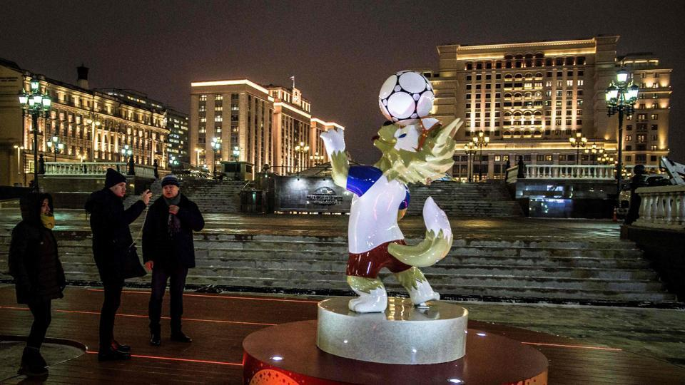 Passers-by take pictures of a figure of Zabivaka, the official mascot for the 2018 FIFA World Cup.  (AFP)