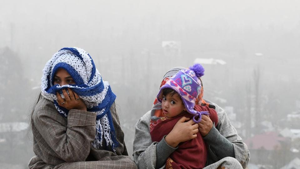A Kashmiri family sits on the outskirts of Srinagar as a cold wave hit Jammu and Kashmir, recording sub-zero temperatures.