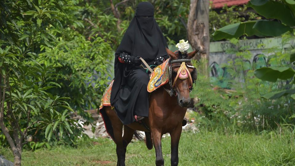 Riding a horse or nailing an archery target is tough at the best of times --it's even harder when you're wearing a niqab. But that isn't about to stop a group of Indonesian women who have banded together to combat prejudice against the face-covering veil, which has been at the centre of a heated global debate over religious freedom and women's rights. One of them is seen riding a horse in Bekasi. (Adek Berry / AFP)