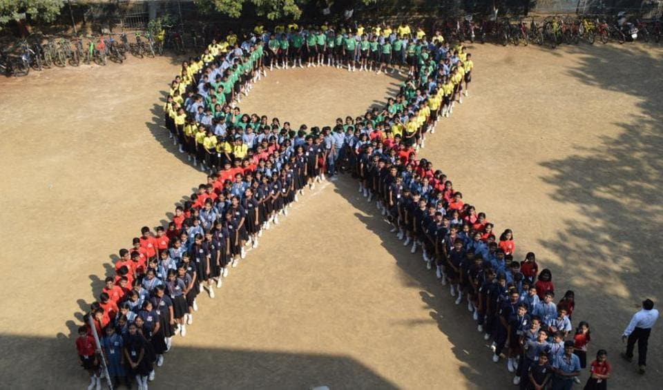 Students assemble in the shape of a 'ribbon' on the eve of World AIDSDay in Thane.
