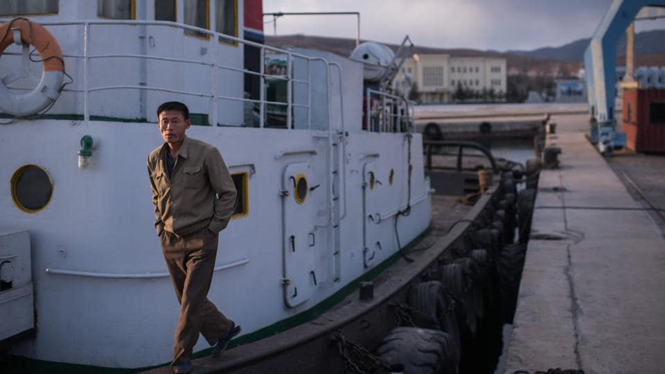 "A sailor stands on his boat at the port in Rason. Foreign firms are given tax, visa and legal concessions --they can set up wholly-owned units, rather than joint ventures-- to lure them to the SEZ, as Kim Jong-Un seeks to pursue a policy of ""byungin"", or ""simultaneous development"", of both the economy and atomic arms. (Ed Jones / AFP)"