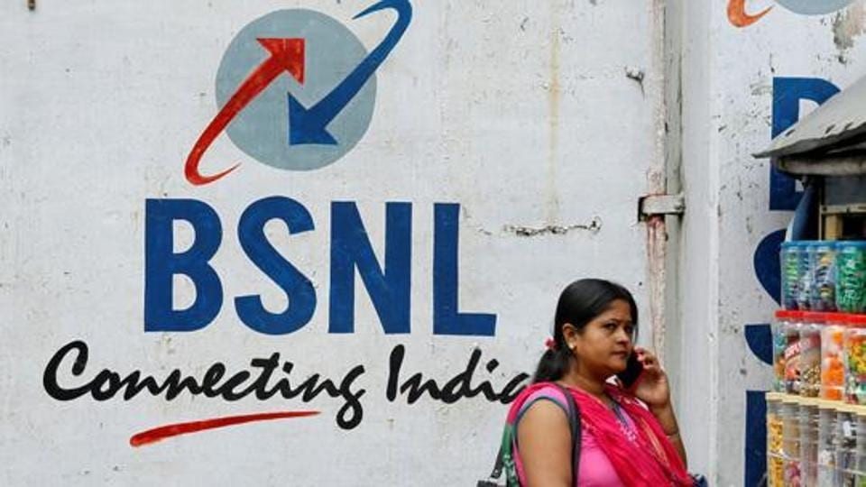 A woman speaks on her mobile phone in front of the logo of Bharat Sanchar Nigam Ltd (BSNL) painted on a wall outside its office in Kolkata on August 24.