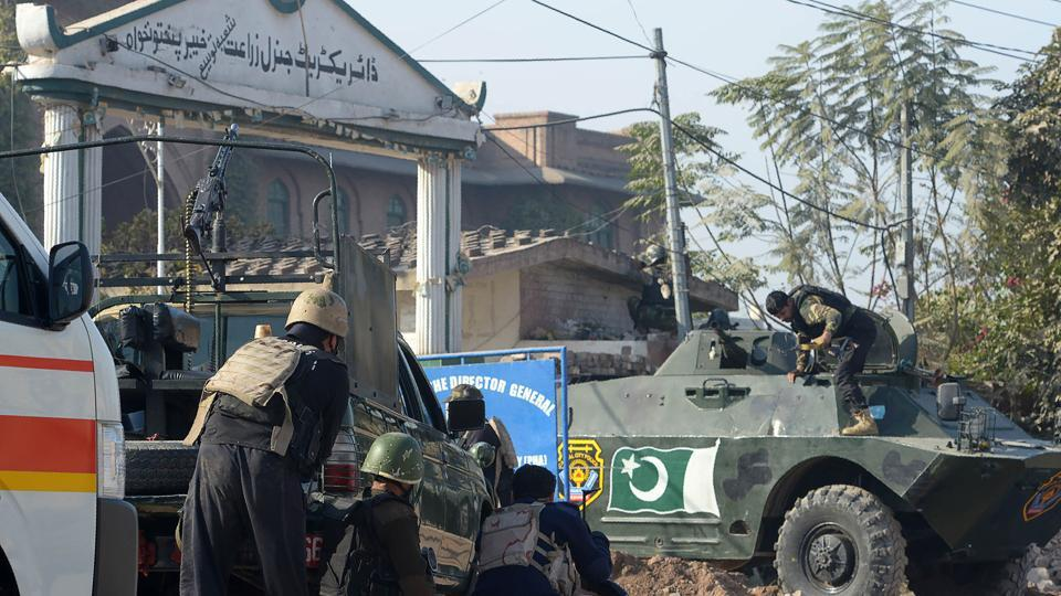 Pakistani security personnel take position outside an Agriculture Training Institute after an attack by Taliban militants in Peshawar on December 1.