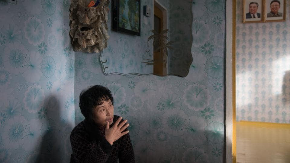 Ra In-Hae, 46, sits in her new home after her old house was damaged by flooding, before the portraits of late North Korean leaders Kim Il-Sung and Kim Jong-Il, near Rason. There used to be more than 5,000 foreign businessmen in Rason, around 80 percent of them Chinese, but officials privately admit some have left. (Ed Jones / AFP)