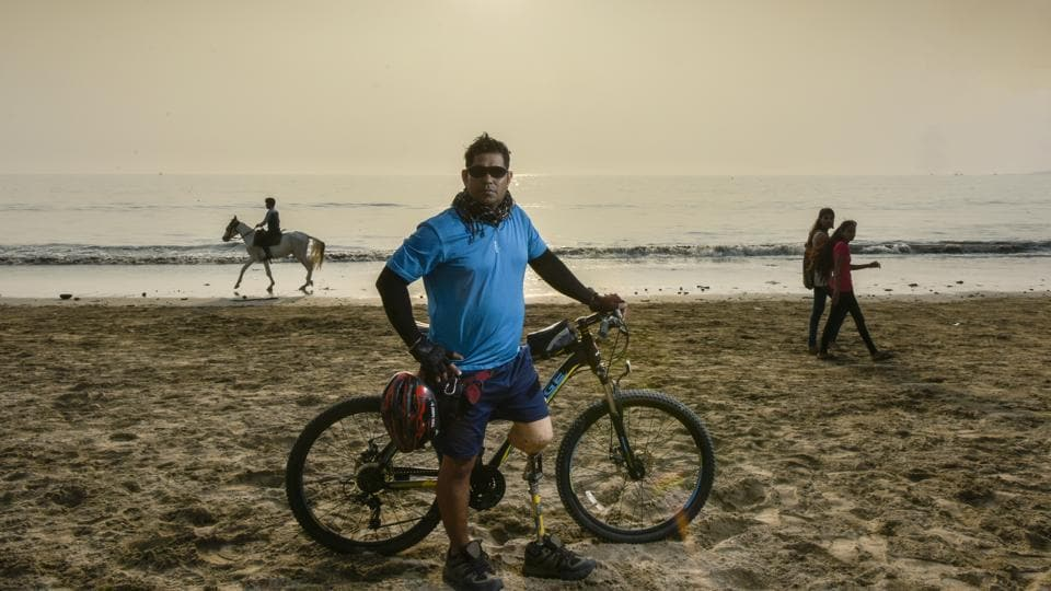 "Vinod Rawat at Versova beach in Mumbai, with his cycle. ""A truck ran over me when I was six. I was hospitalised and because of a sum that my parents could not arrange in time, I lost one of my limbs in a botched up operation that resulted in an amputation,"" he said. Today he's an avid cyclist and sports enthusiast. (Kunal Patil / HT Photo)"