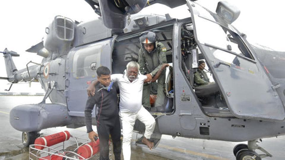 A fisherman who was adrift in the Arabian Sea is escorted down from an Indian Navy helicopter in Thiruvananthapuram after being rescued