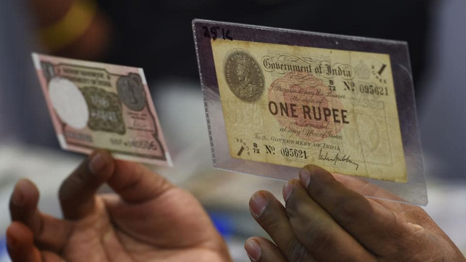 Numismatist Ramesh K. Velunde holds a new Indian One Rupee (L) currency note and an original 100 year-old Indian One Rupee currency note on its 100th anniversary in Mumbai, Maharashtra on November 30, 2017. (Indranil Mukherjee / AFP)