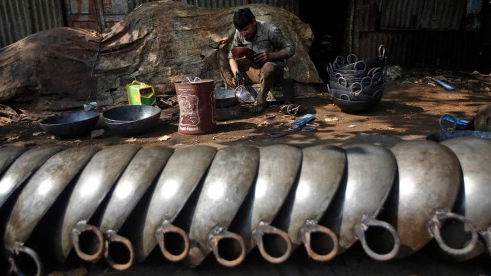 A blacksmith makes iron frying pans at his workshop in an industrial area in Mumbai, Maharashtra on November 30, 2017. (Shailesh Andrade / REUTERS)
