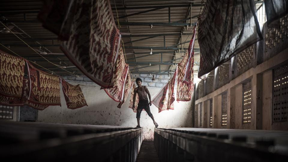 A worker at a sari printing facility skips between troughs in Jetpur, Gujarat. (Satish Bate / HT Photo)