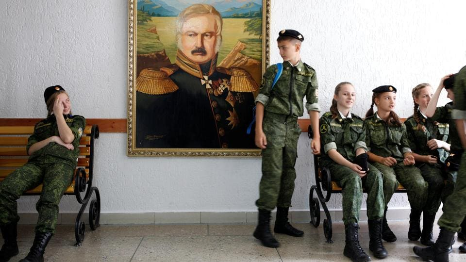 "Students seen at the General Yermolov Cadet School next to the portrait of Alexei Yermolov, the famous Russian imperial general. ""Tomorrow begins today,"" reads the motto of the cadet school that was named after the 19th century general who conquered the Caucasus for the Russian empire. (Eduard Korniyenko / REUTERS)"