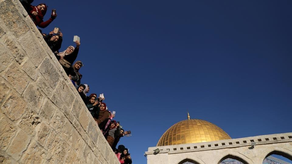 People look on as scouts march and play music in celebration of Mawlid al-Nabi in front of the Dome of the Rock on the compound known to Muslims as Noble Sanctuary and to Jews as Temple Mount, on November 30, 2017 in Jerusalem's Old City. (Ammar Awad / REUTERS)