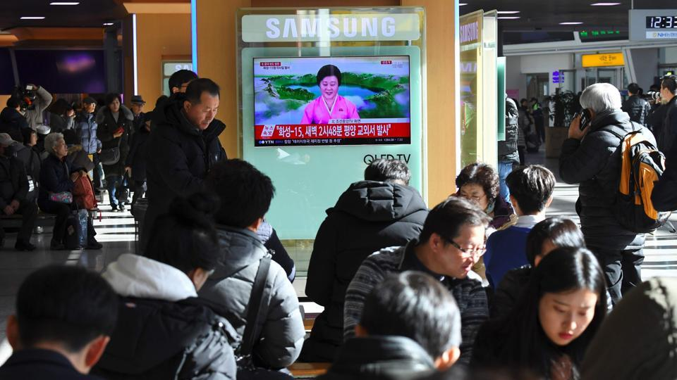 People watch a television news screen showing a North Korean announcer reading a statement on the country's new ICBM test, at a railway station in Seoul on November 29, 2017.