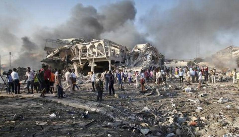 Somalis gather and search for survivors by destroyed buildings at the scene of a huge explosion in the capital Mogadishu, Somalia.