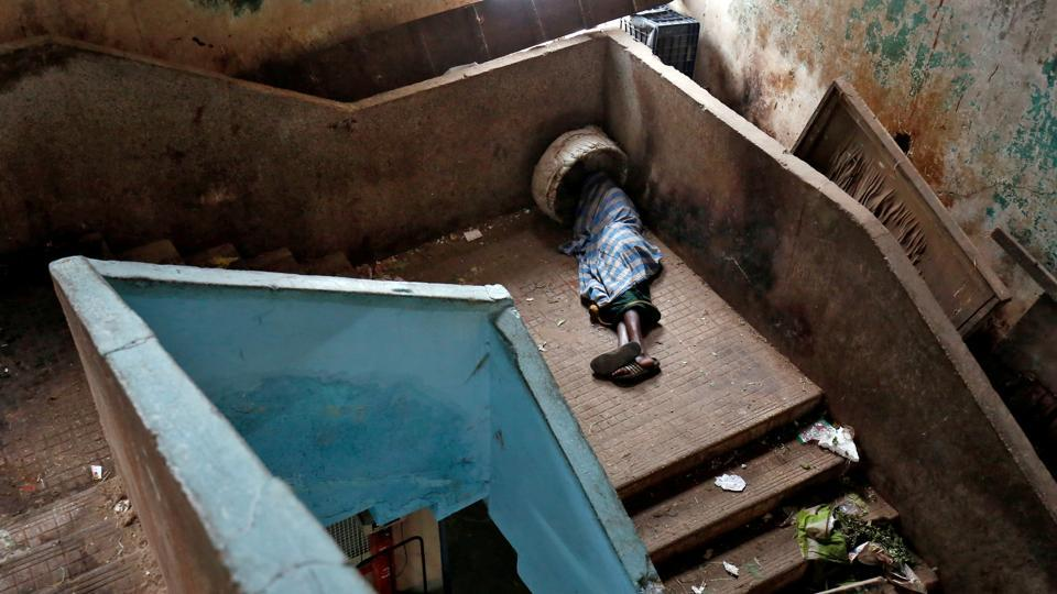 A porter sleeps on a stairway at a wholesale market in Bengaluru, Karataka on November 30, 2017. (Abhishek N. Chinnappa / REUTERS)