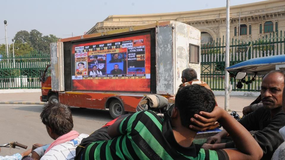 Pedestrians watching live updates of UP Civic polls result on a giant TV screen installed in front of the Vidhan Sabha in Lucknow on December 1.