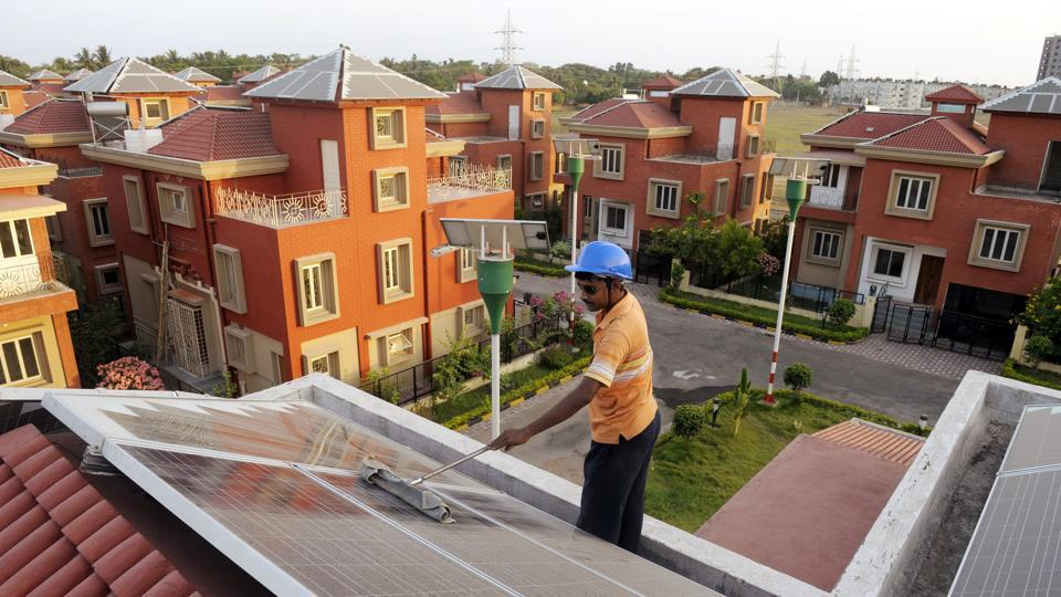 A worker cleans solar panels at a  solar housing complex near Kolkata. For curbing the environmental impact of buildings, electrical demand reduction needs to be supported by electricity generation from green sources.