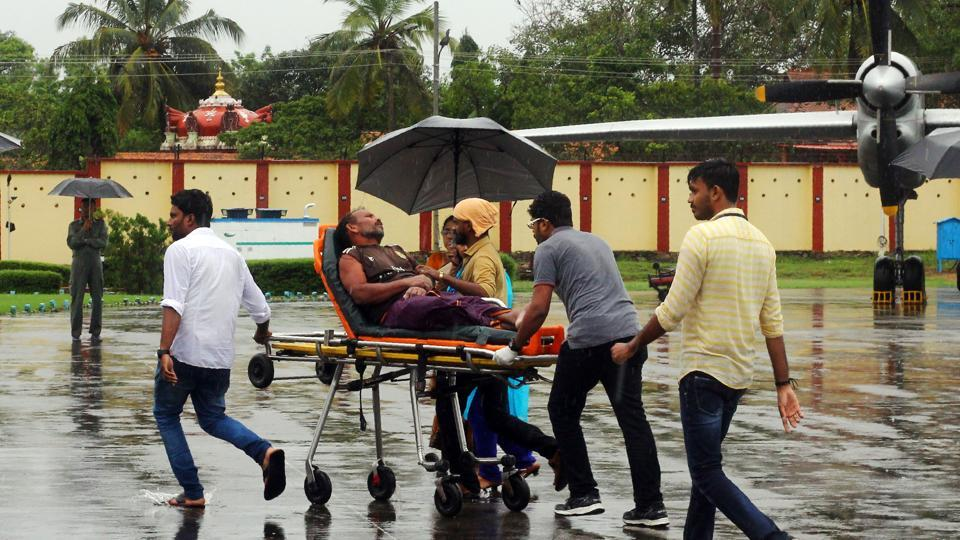 Officials carry a stranded fisherman, rescued by naval and air force helicopters from the Ockhi cyclone, at Thiruvananthpuram airport on Friday.