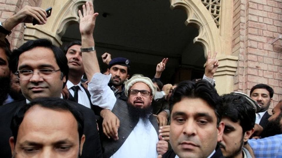 Hafiz Saeed reacts to supporters as he walks out of a court after it ordered his release from house arrest in Lahore.