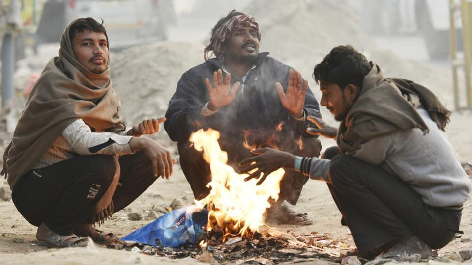 People warm themselves around a fire on a winter morning in New Delhi on November 23.