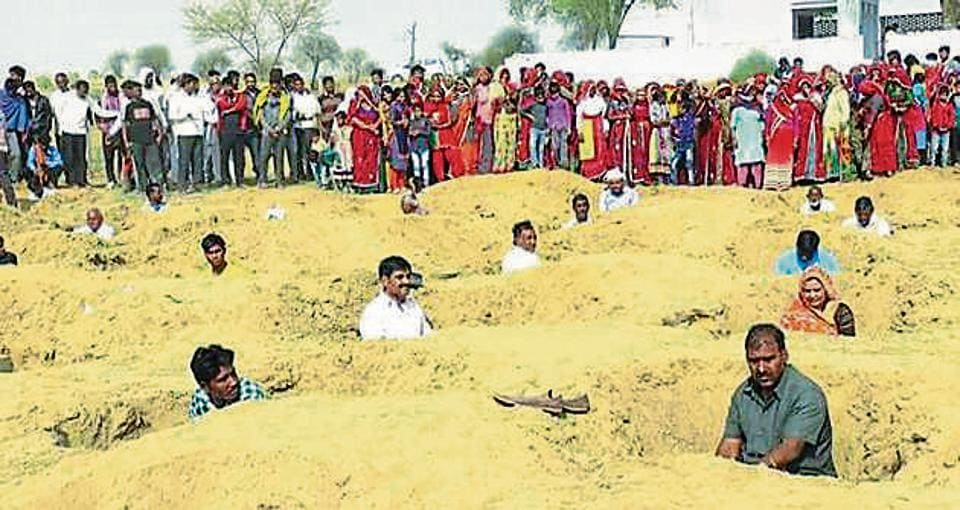 Villagers in Rajasthan's Jhunjunu sit in  2ft deep pits for three hours on Monday as 'token protest' against the local municipal council's plan to set up a waste treatment plant near the village.