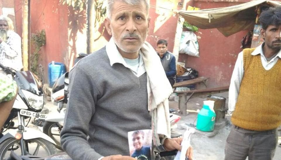 Satish Chandra with a picture of his missing son. The Hathras police have intensified its search after a social activist alerted the police with a tweet.
