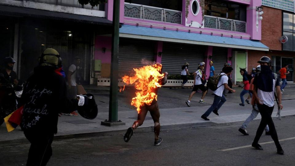 A man accused of stealing was set on fire during a rally against President Nicolas Maduro in Caracas, Venezuela, May 20, 2017. Guns appeared on the streets, and on several occasions security officials were caught on camera firing directly at demonstrators. Police were targeted with homemade explosives. Opposition supporters burned one man alive. (Marco Bello / REUTERS)