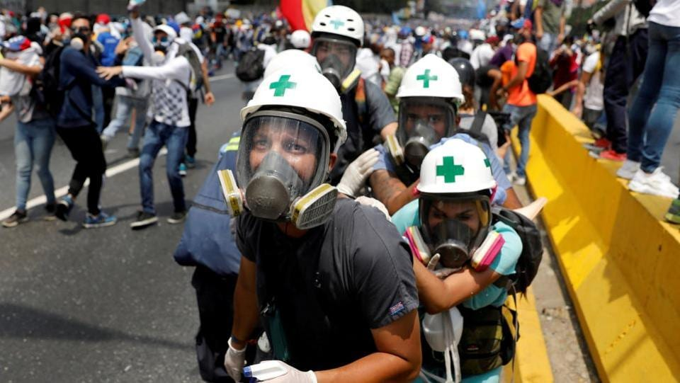 Volunteer members of a primary care response team, huddle together during clashes with security forces at a rally in Caracas, Venezuela on April 26, 2017. Amid raging protests Venezuelans grew accustomed to navigating around barricades and burning streets as they tried to get to school and work. Some days, the country virtually shut down. (Carlos Garcia Rawlins / REUTERS)
