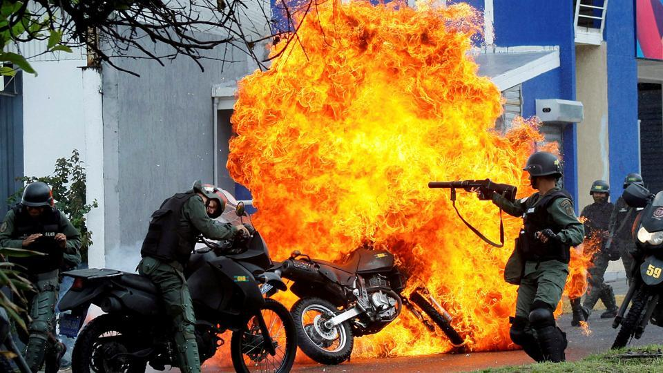 Riot security forces clash with demonstrators as a motorcycle is set on fire during a protest against President Maduro's government in San Cristobal, Venezuela on May 29, 2017. The deaths, injuries and arrests mounted. Over the chaotic months, at least 125 people died, thousands were injured and thousands were jailed. (Carlos Eduardo Ramirez / REUTERS)