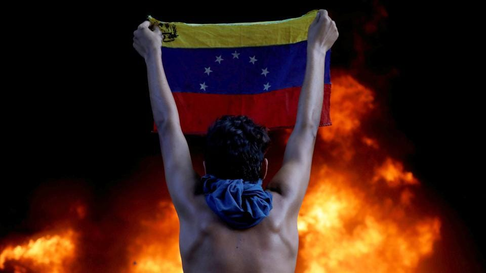 A protestor holds a national flag facing a fire at the entrance of the Supreme Court, during a rally against President Nicolas Maduro, in Caracas, Venezuela on June 12, 2017. Going into a fourth year of crippling recession, Venezuela's 30 million people found themselves skipping meals, suffering shortages of basic foods and medicines, unable to keep up with dizzying inflation, and emigrating in ever larger numbers. (Carlos Garcia Rawlins / REUTERS)