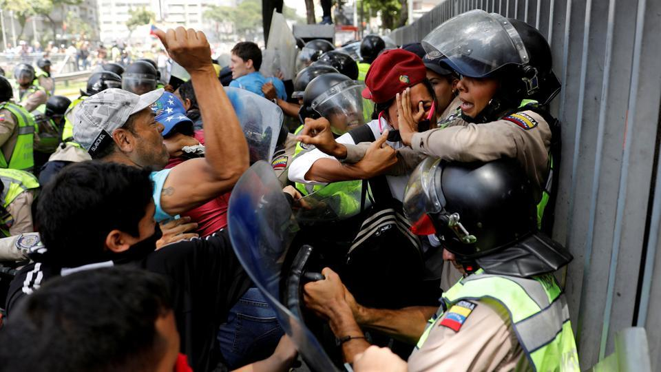 Demonstrators scuffle with security forces during an opposition rally in Caracas. Most recently, in November, Venezuela said it planned to renegotiate its entire foreign debt, adding another dimension to the deepening national crisis. (Carlos Garcia Rawlins / REUTERS)