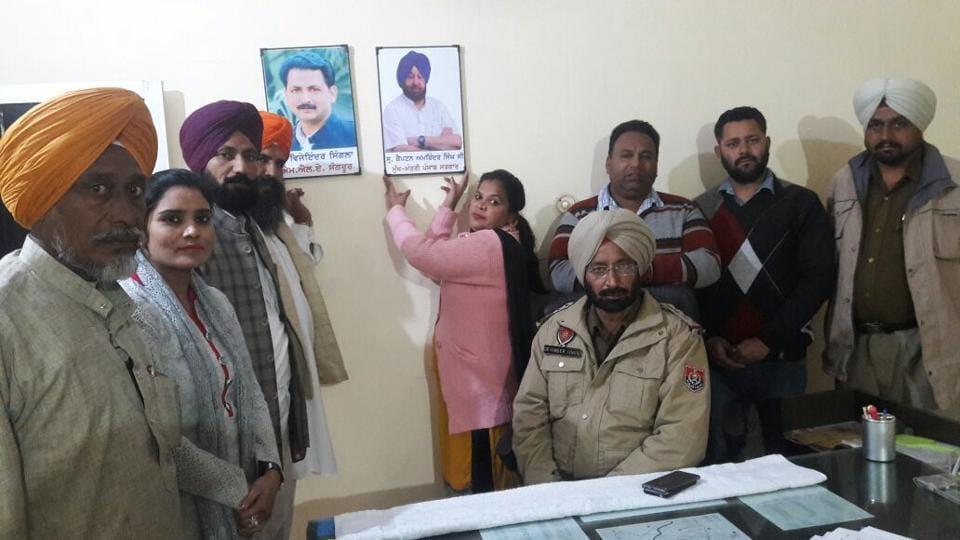 Punjab Youth Congress general secretary Poonam Kangra installing portraits of Amarinder Singh and MLA Vijay Inder Singla at Sangrur police station.