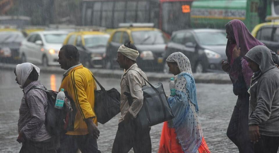 People walk through rain and traffic at Dadar on Tuesday morning.  (Pratik Chorge)