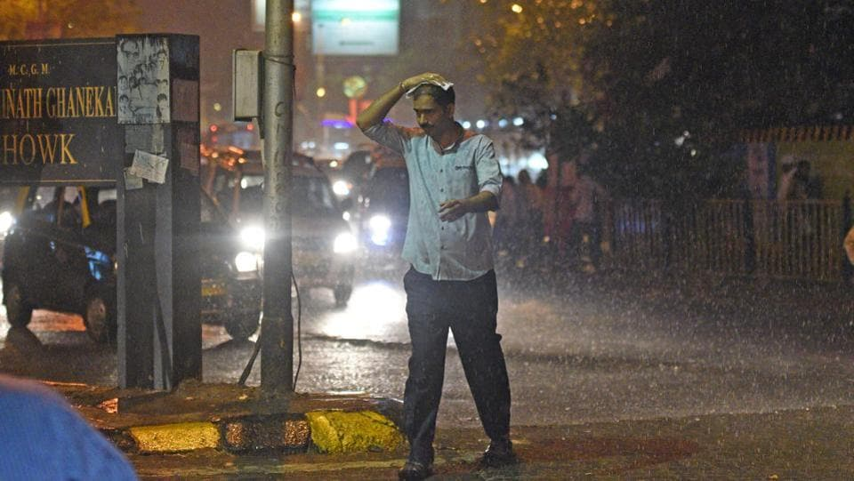 A man crosses a road during rainfall at Dadar in Mumbai on Monday night. Maharashtra closed down schools and colleges, including those in Mumbai and adjoining areas in the wake of forecasted rain triggered by Ockhi on Tuesday. (Satyabrata Tripathy / HT Photo)