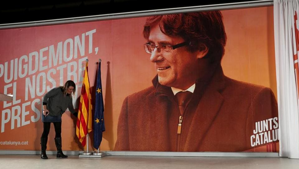 A woman arranges flags in front of a backdrop of ousted Catalan President Carles Puigdemont before a press conference by former Catalan cabinet members Jordi Turull and Josep Rull who were released from jail on bail in Barcelona.