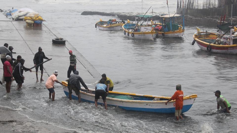 Fisherman pull their boats as Cyclone Ockhi strikes Worli, Mumbai.