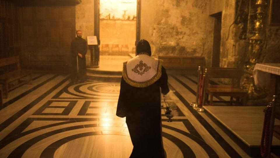 An Orthodox Christian priest walks inside the Church of the Holy Sepulchre in Jerusalem's Old City. As night falls, Adeeb Joudeh, a Muslim, makes his way through the stone alleyways of Jerusalem's walled Old City cradling the ancient key to one of Christianity's holiest sites. (Ronen Zvulun / REUTERS)