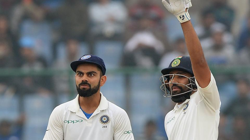 Virat Kohli (L) and Rohit Sharma (R) gesture towards the dressing room during the fourth day of the third Test cricket match between India and Sri Lanka.