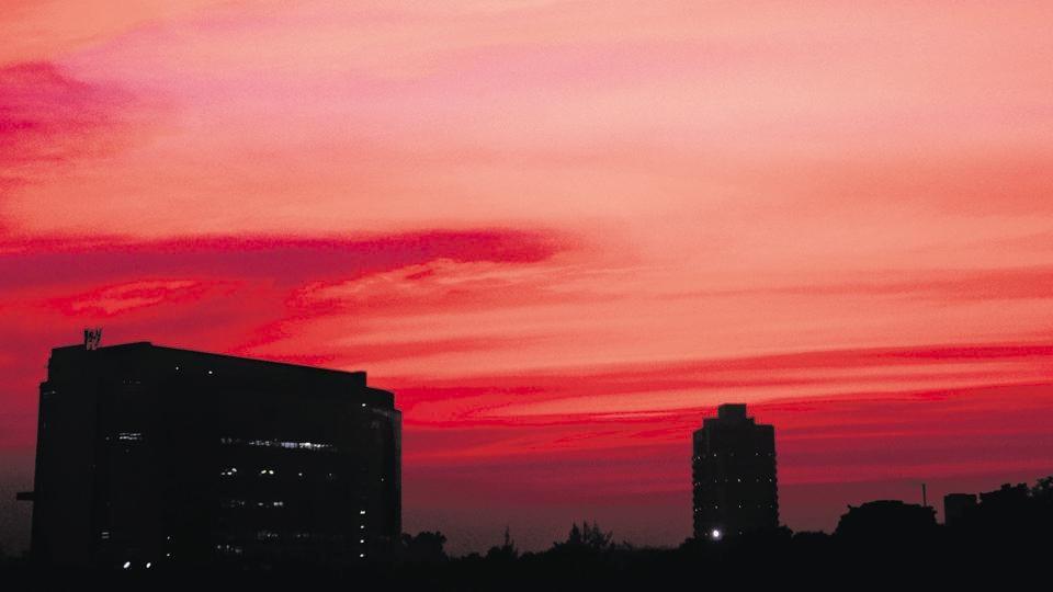 The setting sun's rays spread a crimson hue as they sieve through a cloudy sky over the Mohali industrial area on Monday.