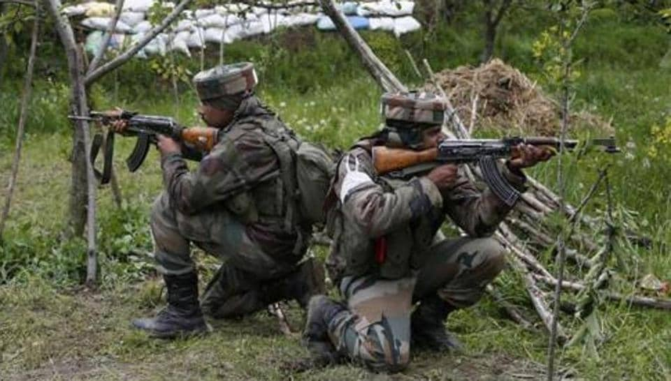 Soldiers take position in an apple orchard during a search operation in Shopian in Kashmir  during an anti-insurgency operations.