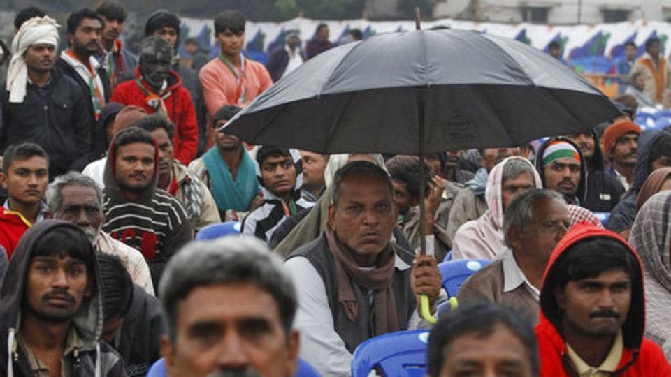 A Congress supporter holds an umbrella to protect from rain during an election rally at Dhrangadhra in Surendranagar district of Gujarat on Tuesday.