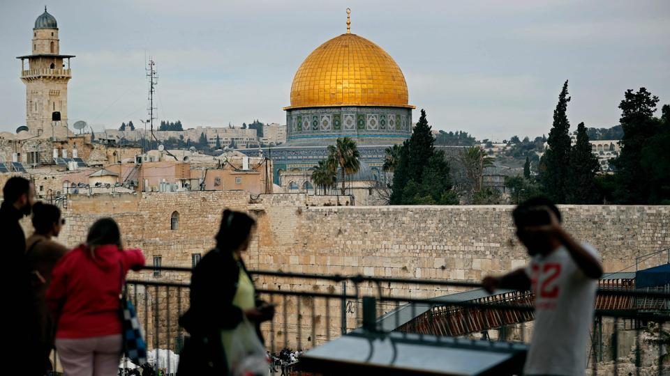 People look out at a view of the Old City of Jerusalem, with the Dome of the Rock (C) in the Al-Aqsa mosque compound and the Western Wall below on December 5, 2017.