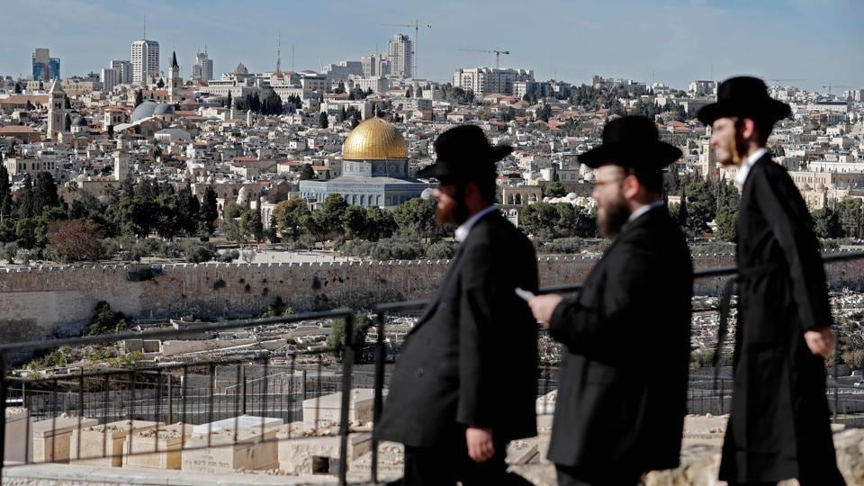 Ultra Orthodox Jews are seen walking in the city of Jerusalem in the Mount of Olives with the Dome of the Rock mosque in the background