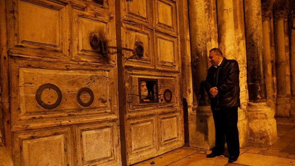 "Adeeb Joudeh (R), looks at a priest as he peers through an opening in the church doors as they prepare to open it, in Jerusalem's Old City. ""I started learning this when I was eight years old. It's handed down from father to son,"" said Joudeh. ""I have been doing this for 30 years and I feel that the Church of the Holy Sepulchre is my second home.""  (Ronen Zvulun / REUTERS)"