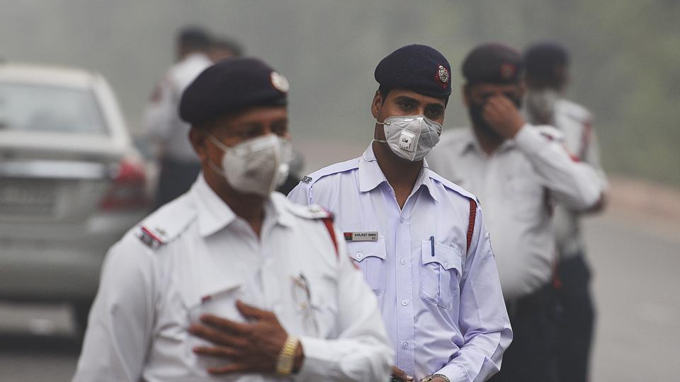 Delhi traffic police officers are seen wearing a face mask at an intersection in New Delhi, on November 11, 2017.