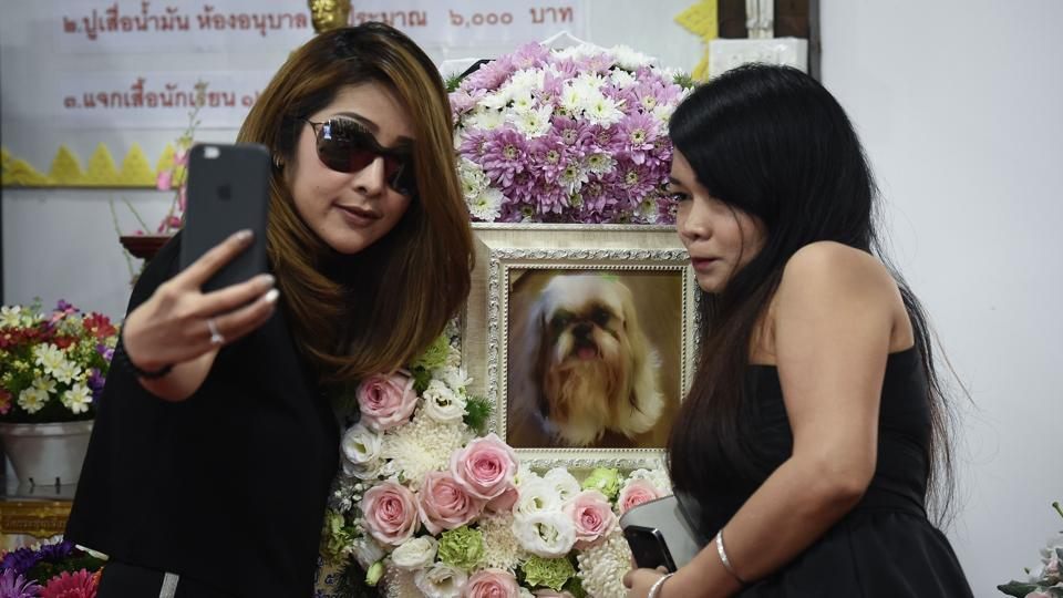"Pimrachaya Worakijmanotham (L) and her friend take a selfie with a photo of Dollar, her six-year-old Shitzu, during the pet's funeral. ""This is the last time I can be with her... so I want Dollar to receive good things,"" Pimrachaya, dressed in black and wearing sunglasses, told AFP, a framed photo of ""her child"" Dollar behind her. (Lillian Suwanrumpha / AFP)"