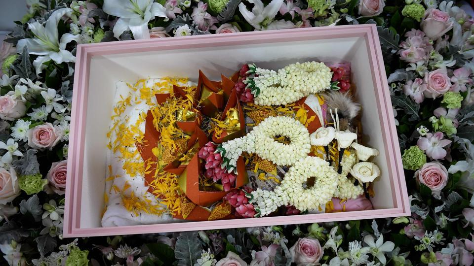 "Dollar, inside a coffin with flower garlands and gold joss paper during her funeral. ""In this life, she (Dollar) couldn't go to the temples to make merit for herself. This is the only thing we can do for her,"" Pimrachaya, who is a banker, said. (Lillian Suwanrumpha / AFP)"
