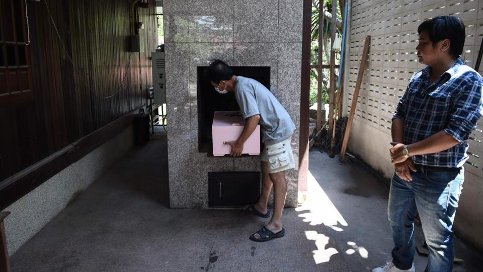 An undertaker places a coffin inside a crematorium in Bangkok. While it makes for a good business -- starting prices are around 3,000 baht (around $91) and the most extravagant services cost up to 100,000 baht -- the monk says the funerals have brought people closer to religion. (Lillian Suwanrumpha / AFP)