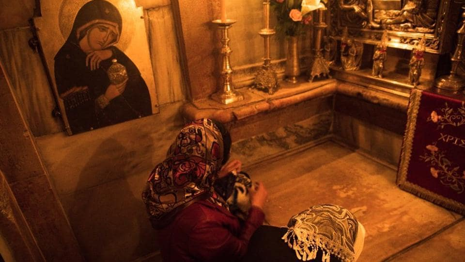 Worshippers touch the purported tomb of Jesus in the burial place, known as the Edicule, at the Church of the Holy Sepulchre. Jerusalem's Old City today houses sites that are sacred to all three major monotheisms. It and other east Jerusalem areas were captured by Israel from Jordan in the 1967 Middle East war. (Ronen Zvulun / REUTERS)