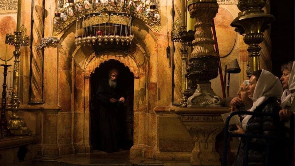 Worshippers stand nearby as a priest peers out from the Edicule, the burial place housing the purported tomb of Jesus, at the Church of the Holy Sepulchre. The Greek Orthodox, Armenian and Roman Catholic denominations share custody of the church, where tensions often run high over control of its various sectors. (Ronen Zvulun / REUTERS)