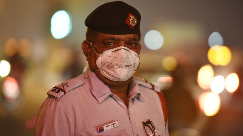 A traffic police man is seen wearing a breathing mask which have been provided to traffic personnel by the department. These policemen spend anywhere between 12 to 14 hours a day managing traffic on the congested roads of Delhi, where air pollution levels average three to four times above levels considered safe during this time of the year. (Raj K Raj / HT Photo)